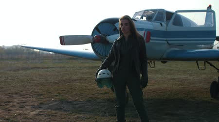 girl stands on the background of the plane in the image of a pilot holds a helmet in a leather jacket Stock mozgókép