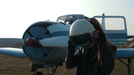 close-up of a girl on the background of an airplane who puts on a pilot helmet and looks into the camera