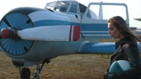 a girl in the guise of a pilot walks against the background of an airplane wing and looks at the camera