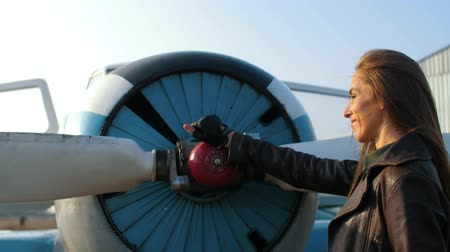 a girl in the image of a pilot wipes an airplane engine with a glove