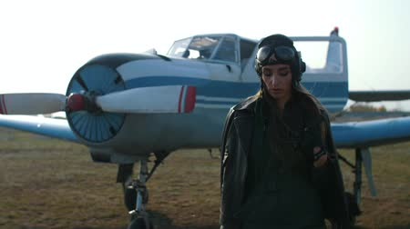 girl pilot in a special hat on which glasses and a leather jacket stands out of defocus, on a close-up and looks at the camera Stock mozgókép