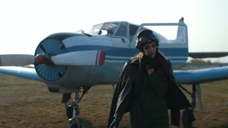 girl pilot, in a special hat on which glasses and a leather jacket stands with a walkie-talkie departs from the plane in the background comes to the fore and looks into the camera Filmati Stock