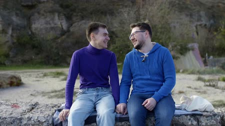 two gay guys from the LGBT community, sitting on a stone pier in a sweater and sweatshirt and scrubbing while holding each others hands