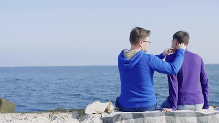 two gay guys from the LGBT community are sitting on a stone pier against the background of the sea, and one straightens his collar to the other