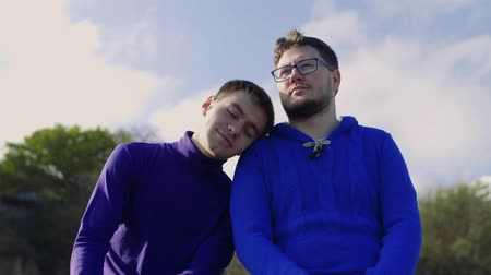 close-up, two gay guys from the LGBT community, cute sit and look into the distance, and one gently puts a stake on his shoulder to his partner. Panorama up