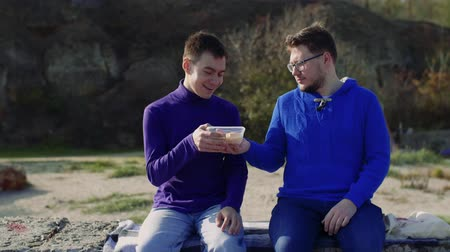 two gay guys from the LGBT community are sitting in nature and one is treating the other with a meal Stock mozgókép