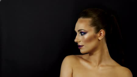 close-up, girl model with golden make-up posing on a black background and looking at the camera