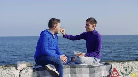 one gay man feeds a sandwich on a stone pier amid a sea of another gay