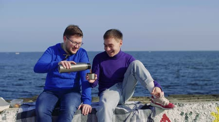 two gays amid seagulls and the sea pour tea from a flusk and laugh