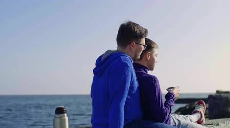 two gays sit against the sea, drink tea from a flusk, smile, look at each other, relax, smile and look into the distance