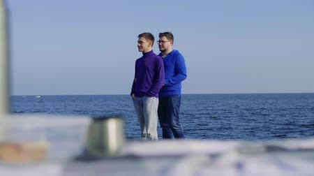 a picnic on the sea two men from the LGBT community, one approaches his boyfriend, hugs him, they look at each other and smile, shifting focus from the litter on which butyrbrod and a flusk