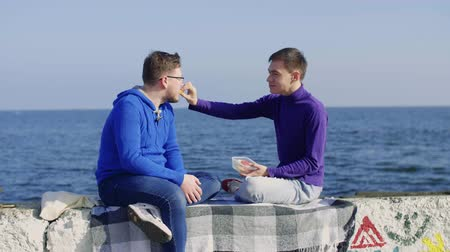 one gay man feeds a sandwich on a stone pier painted with graffiti by hooligans against the backdrop of a sea of another gay