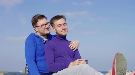 two gay men are sitting on a picnic hugging and smiling against the sky in sportswear in their hands a thermos mug