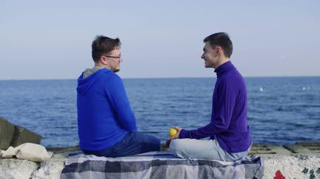 two guys are sitting on the background of the sea, one passes the other a yellow apple Stock mozgókép