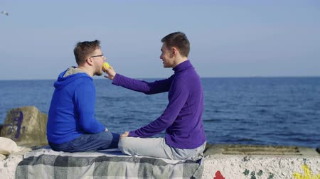 two gay men sit on the background of the sea, one bites and then passes the other a yellow apple