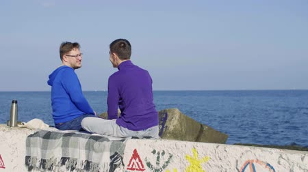 two gay guys sit on the background of the sea and reach for a kiss Stock mozgókép