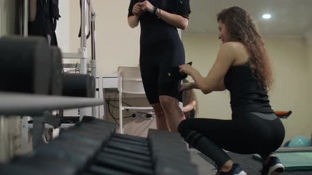 girl trainer in a sports figure sits down and fastens special pads on the EMC suit on the girls legs before a fitness training Dostupné videozáznamy