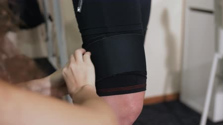 rozjařenost : girl coach fastens special pads on the EMC suit on the girls legs before a fitness training