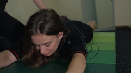 kifejező pozitivitás : close-up of a girl in a suit for EMS training, doing exercises called a boat lying on his stomach lying on his stomach to raise legs and torso, and a girl trainer with a sports figure helps