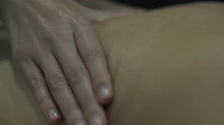 performs massage with female hands on the tired skin of a girl where there are traces of clothing