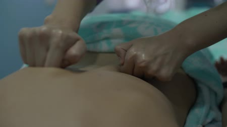 performs massage movements with fists of the phalanges of the fingers on the female back, female hands