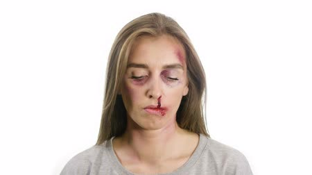 taciz : portrait of a woman on a white background, with traces of domestic violence, bruises of a sadina, blood from the nose on her lips, the girl looks at the camera then does not look and then looks again