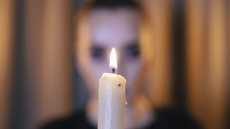 cartomante : close-up of a burning candle on the background of a woman who blows out a candle