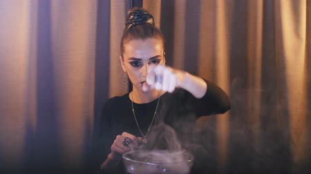 psicodélico : a witch over a bowl with a potion from which smoke comes out makes magical movements with her hands and looks into the camera