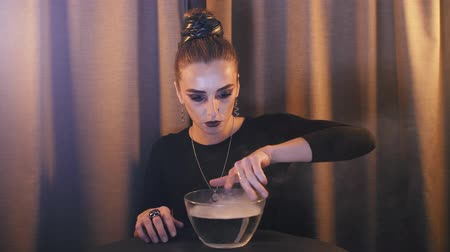 psicodélico : a witch over a bowl with a potion from which smoke comes out makes magical movements, with her hands and looks at the camera and smiles