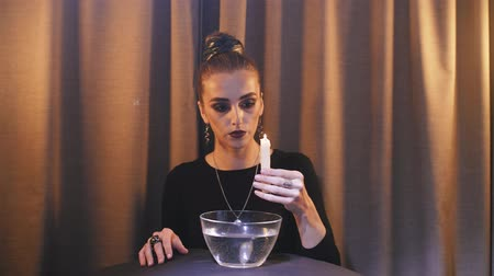 feiticeiro : a psychic performs a divination ritual over a bowl of water, using paraffin dripping into water Stock Footage