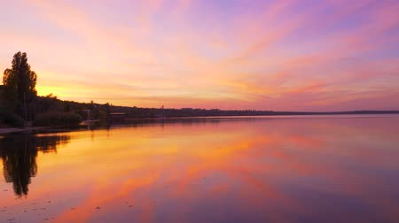 древесный : landscape reflection in the sea water of a beautiful gradient iridescent colors of orange and purple, sunset sky, as in the picture