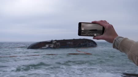 woman s hand holds the phone, takes off a cargo ship turned over at sea not far from the coast