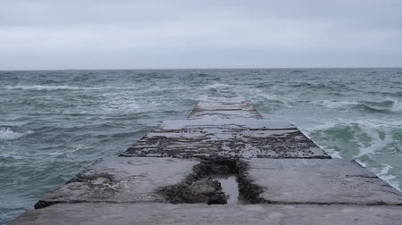 symmetrical frame of a broken pier against the background of the sea in a slow mo, strong wind and flying gulls