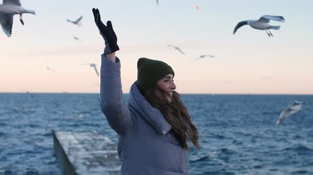 beak : girl in gray down jackets on a background of a stone pier in the sea, surrounded by flying gulls, smiles slightly with a raised hand up and looks at the camera