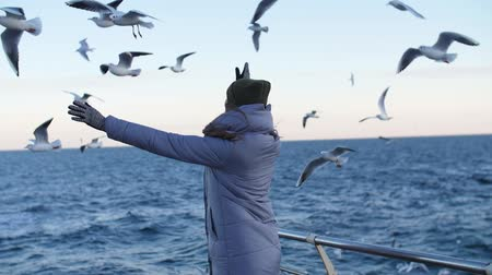 girl in a warm jacket with hands up against the background of flying seagulls at sea