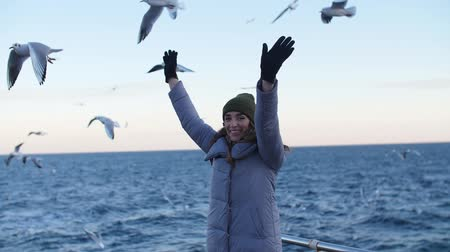 a girl in a hat with gloves and a warm jacket, waving her arms smiling broadly against the background of flying seagulls at sea, turns and looks at the camera