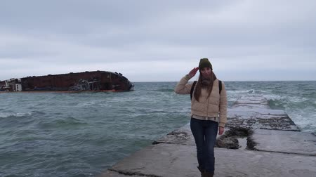 obsoleto : on a sea pier near the shore, a girl in a hat and a jacket salutes against the background of an inverted cargo ship