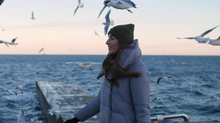 girl in a warm jacket surrounded by seagulls