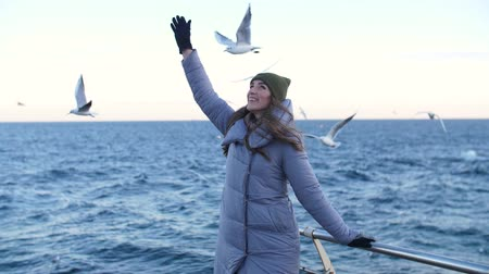 girl in a gray down jacket, reaches out for seagulls flying in the background in a slow motion