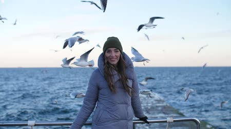 girl on the background of the sea and about flying seagulls in the slow mo turns and playfully smile at the camera