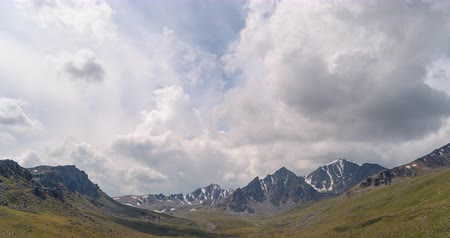 snow on grass : The clouds over the peaks of Kyrgyzstan. Zoom. Time Lapse