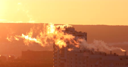 ural : Smoke from the pipes in the high-rise residential building, early morning, backlight. Telephoto lens. Mirage in the atmosphere Stock Footage