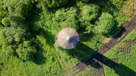 camera rotation : Rise above the water tower with rotation. HEAD OVER SHOT. View of the dirt road, meadow, bushes and potato field., From Dron Stock Footage