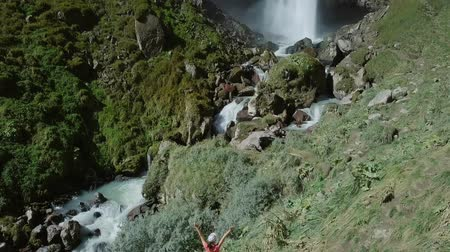 ágil : Elbrus region. Girl on the background of a waterfall. The Sultan waterfall on the Kyzyl-Su river. Aerial view. Kabardino-Balkaria, Russia, From Dron