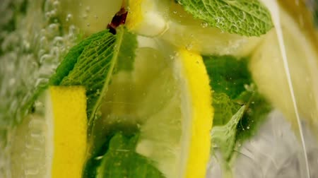 lemoniada : Lemonade with lemon and lime pouring in slow motion