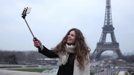 took : Girl taking selfie at the Eiffel Tower