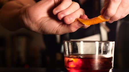 паб : Barman Squeezing Orange Peel on Negroni Cocktail Стоковые видеозаписи