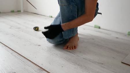 laminát : A young hipster is doing repairs at home. The man is laying the laminate floor.