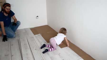 laminát : Dad and daughter are doing repairs in the apartment. Laminate laying.