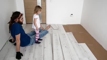 laminált : Dad and daughter are doing repairs in the apartment. Laminate laying.